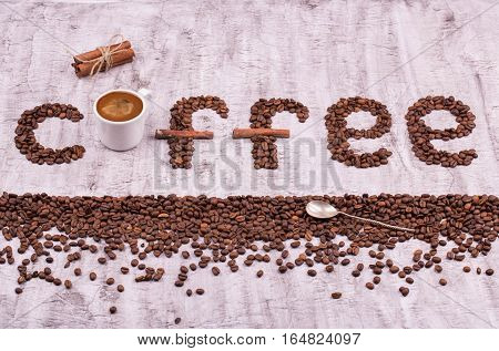 Coffee. An inscription from coffee grains. Letters from coffee grains. Coffee grains in the form of letters on a concrete background