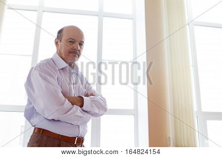 elderly man in white shirt standing at the window in the office. Angry chief glance downwards