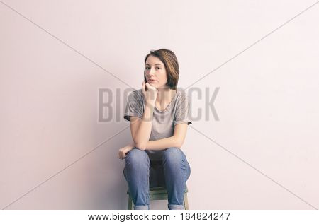 Beautiful, slim girl sitting on a stool and looking confidently forward. Lens flare effect