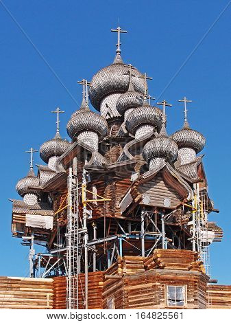 KARELIA KIZHI RUSSIA - June 2014: North Russian wooden architecture - open-air museum Kizhi. Church of the Transfiguration 1714. Restoration of the method of lifting. The whole structure is held due to the internal metal frame.