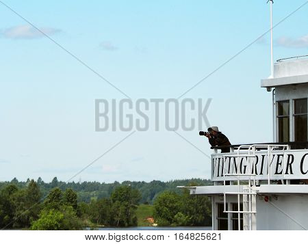 MOSCOW REGION RUSSIA - JUNE 2016: The tourist with a camera is shooting from the upper deck of cruise liner. Travel photographer with digital camera making photo of the nature.