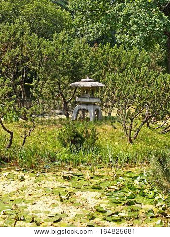 MOSCOW RUSSIA - JUNE 2013: Botanical Garden to them. NV Tsitsin RAS. Japanese garden. Japanese stone lantern Toro (Yukimi-Doro) on an island in the pond.