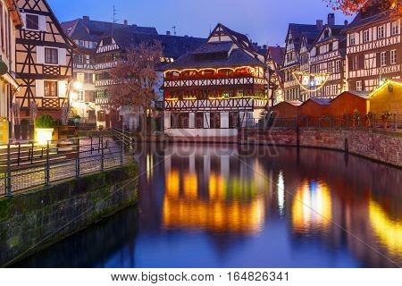Traditional Alsatian half-timbered houses with mirror reflections in Petite France during twilight blue hour, Strasbourg, Alsace, France