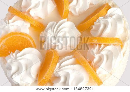 Souffle cake decorated with marmalade fruits and cream closeup