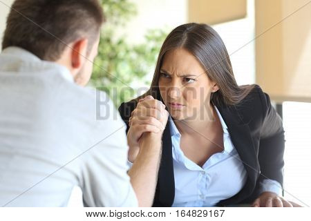Two angry businessman and businesswoman wearing suit fighting looking each other at office