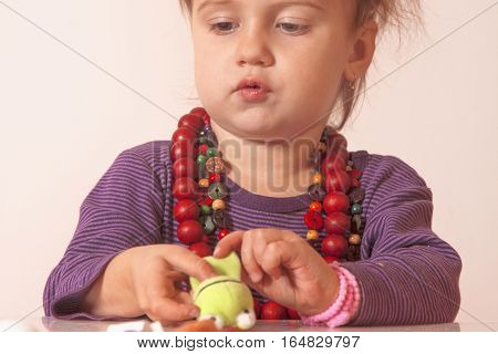 little cute girl playing indoorswith colored toys (developmental toys for children)
