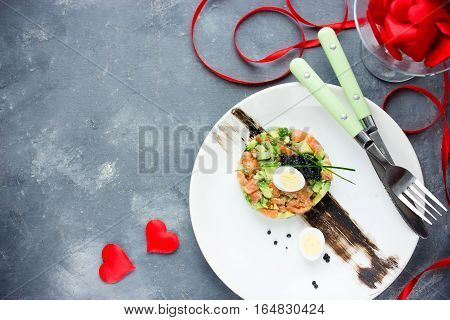 Salmon tartare with avocado black caviar and quail egg on Valentines Day aphrodisiac food for lovers festive delicacy appetizer romantic seating place