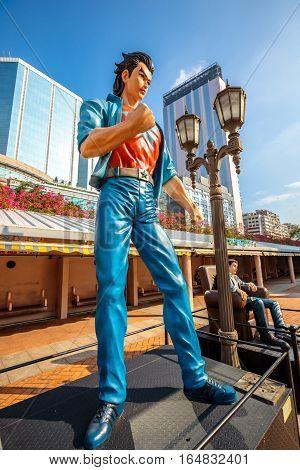 Hong Kong, China - December 5, 2016: Wang Xiao Hu, statues of famous characters, in Hong Kong Avenue of Comic Stars, Kowloon Park. Urban skyline background of Tsim Sha Tsui District.
