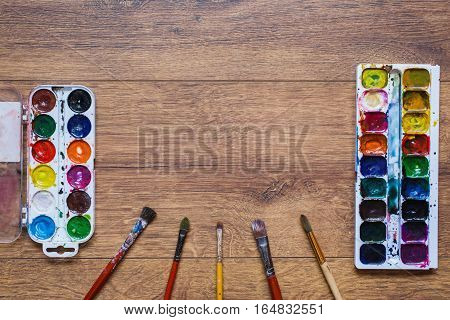 Artistic squirrel brush and water paints. Drawing tools for pupils students artists .Palitra of twenty-four colors. . Economical and safe material for painting with children. Brushes and watercolor on warm wooden background.