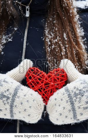 Woman in in mittens holding red rattan heart, Valentines Day concept.