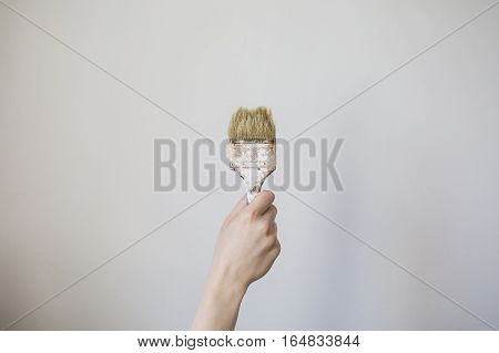 Paint brush with a wooden handle in a man's hand on a light background. Home repairs . Concept. The tool for painting of walls. Dirty brush in gray wall