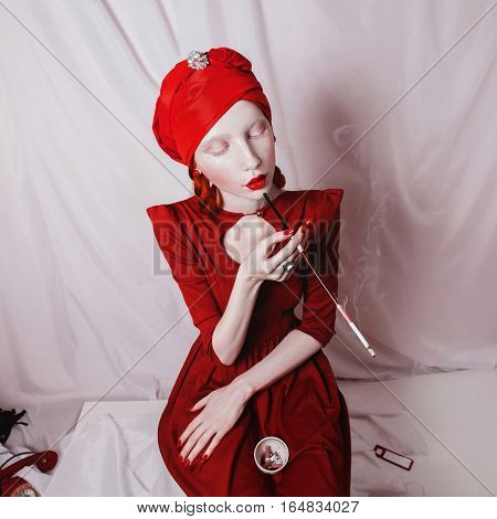 redhead smoking girl with red lips and a red turban on a white background woman with a white skin with a ring on her finger and a mouthpiece in hand a bright unusual appearance albino
