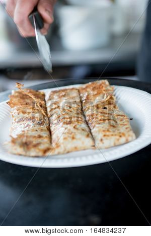 Crepe In Paper Plate Sliced Into Three With Knife