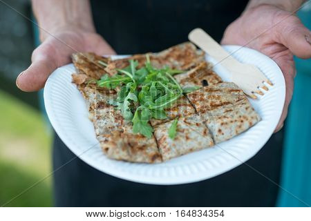 Hands holding cut crepe in paper plate