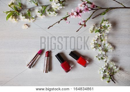 Lipstick and nail polish purple and red flowers. Tools for creating a flirtatious and attractive image. Persistent cosmetic products for painting. Cosmetics surrounded by white and pink flowers.