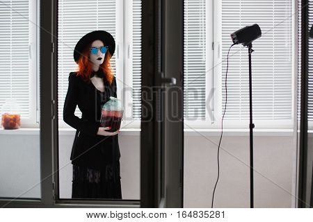 Portrait of red-haired girl in bow tie on a dark background gothic style girl in black clothes sense style fashion girl in a black cloak coat black lips round glasses hat blinds on the balcony
