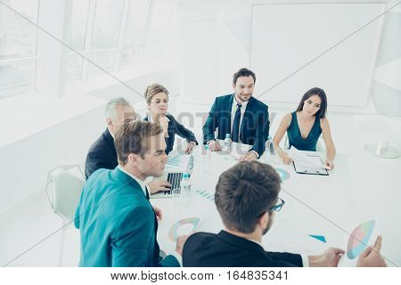 Group Of Confident Co-workers Consulting At Meeting In Office