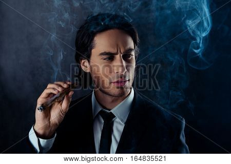 Young Handsome  Man Holding Cigar On Dark Background