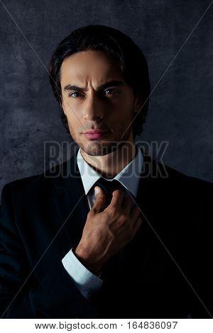 Portrait Of Serious Handsome Businessman Correcting His Black Tie