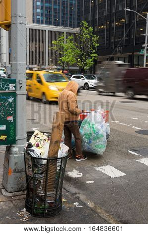 NEW YORK - MAY 3 2016: Unknown homeless person collecting plastic bottles and empty soda cans for a little money