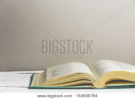 Open book on wooden background. Back to school. Copy space. Toned retro image