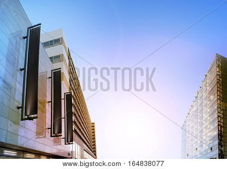 Blank black vertical banners on building facade, design mockup. Store flags mock up on the street. Outdoor flagpole template on the side of the shop exterior. Three signages hanging the wall.