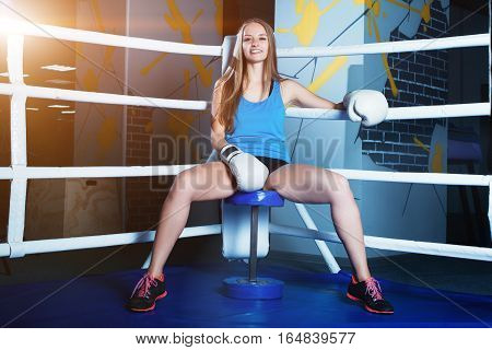 Attractive Young Woman With Blue Boxing Gloves Sitting In The Corner Of Boxing Ring.