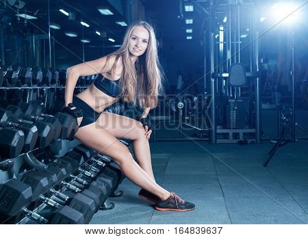 Blonde Fitness Woman In Sportswear With Perfect Body Posing In The Gym. Attractive Sporty Girl Resti