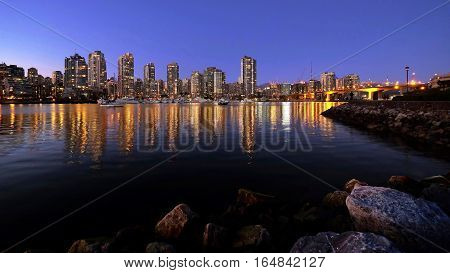 Night city lights reflections in calm water of Falce Creek. Downtown Vancouver from Kitsilano.  Yaletown. Cambie Bridge. British Columbia. Canada.