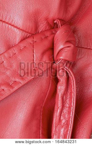 Knotted belt on a woman's red leather coat.