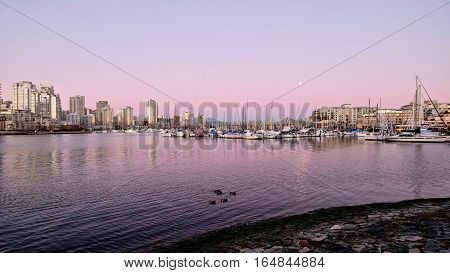 Pink sunset and full moon over boats in the marina. Kitsilano and Cambie bridge. Vancouver. British Columbia. Canada.