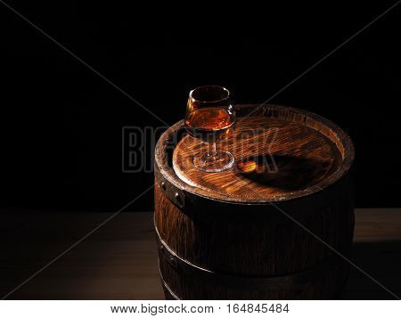 Glass Of Cognac With Barrel On Wooden Backgroun