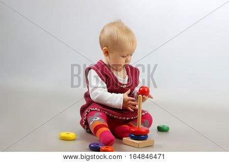 Adorable baby girl in red dress playing with some wooden toys.