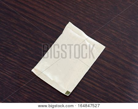 Brown bag of sugar on wood table.