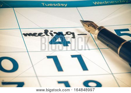 calendar with black pen focus on text meeting