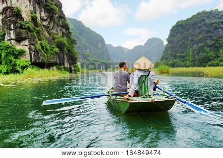Tourists In Boat, Vietnam. Rower Using Her Feet To Propel Oars