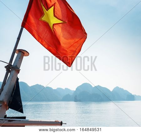 Closeup view of the flag of Vietnam (red flag with a gold star) fluttering on blue sky background in the Halong Bay of the South China Sea Vietnam. The Ha Long Bay is a popular tourist destination.