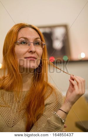 Young woman in glasses thinking in the library, telephoto