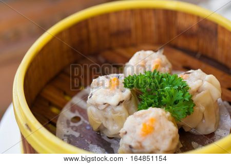 Chinese steamed dumpling or Dim sum stuffed with minced pork decorated in bamboo made steamer local style.