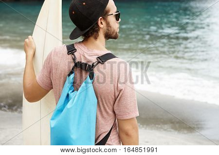 Handsome Young Caucasian Beginner Surfer With Beard Standing In Front Of Blue Ocean And Waiting For