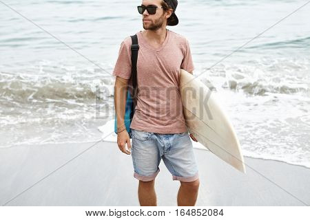 Attractive Young Surfer Wearing Trendy Shades And Snapback Holding Surfboard Under His Arm, Standing