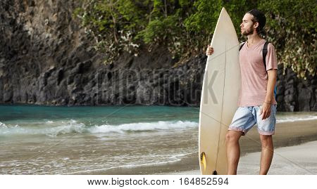 Young Attractive Bearded Male Standing With Surfboard On Exotic Beach And Looking Into Distance, Tur