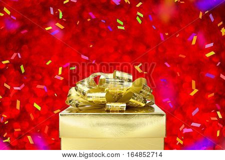 Close Up Golden Present Box With Big Bow And Blowing Colorful Confetti At Red Bokeh Blur Background,