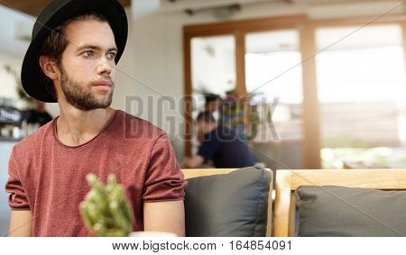 Indoor Portrait Of Handsome Hipster In T-shirt With Rolled Up Sleeves Relaxing Alone At Cafe And Loo