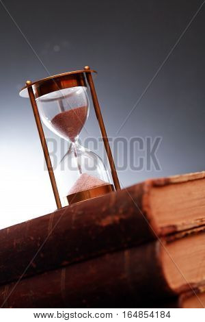 Vintage still life. Closeup of hourglass on old book