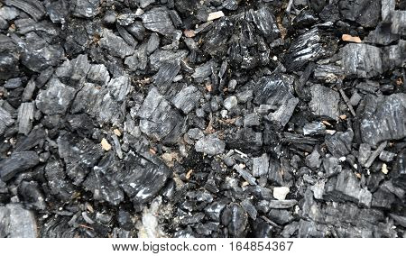 Extinct coals after bonfire. Ashes and cinders from waste burning. Black ashes or charcoal texture wallpaper. Burnt wood. black charcoal as background. The ash background.