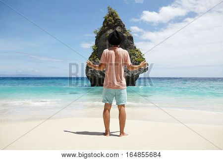 Rear View Of Tourist In Trendy Hat Holding Arms Wide Open In Front Of Rocky Island With Tropical Veg