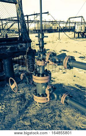 Group of wellhead. Oilfield with sand ground. Oil and gas . Toned.