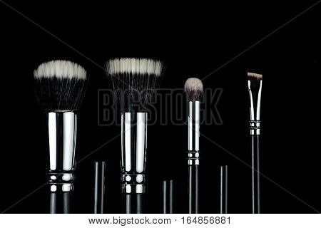 Makeup brushes lying on a black background