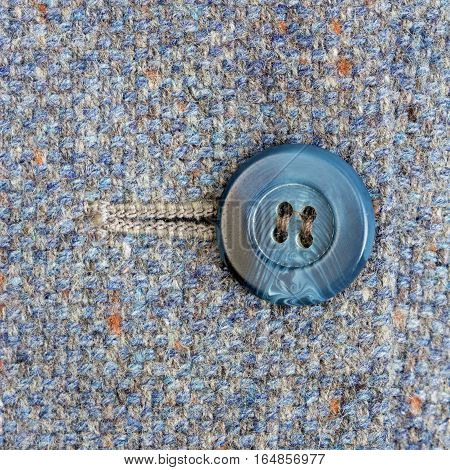 A mottled blue button and button hole on tweed fabric.